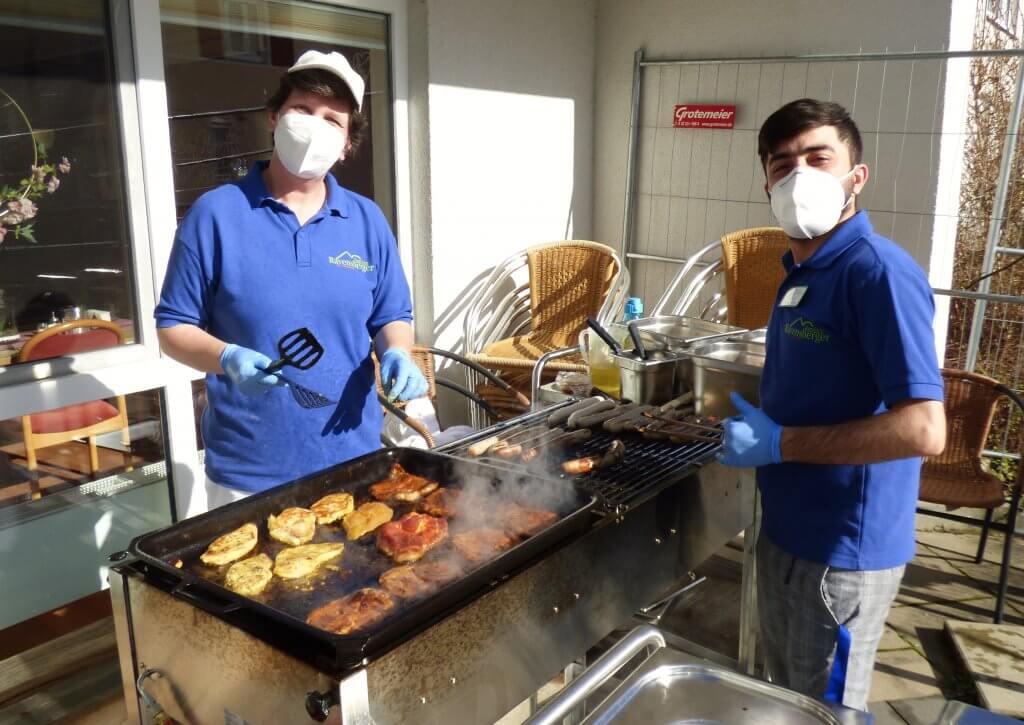 Mitarbeiter beim angrillen des Fleisches