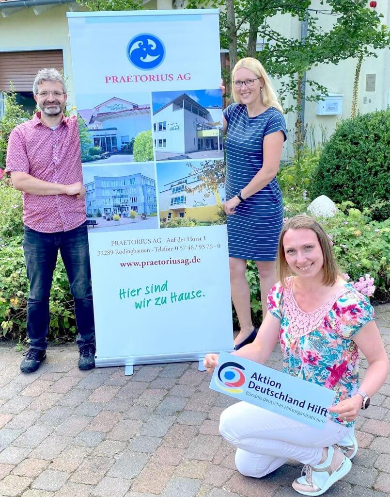 Zwei Frauen und ein Mann zeigen dei Werbebanner der Praetorius AG und der Aktion Deutschland hilft